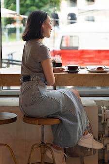 Volledig geschoten vrouw zitten met koffie