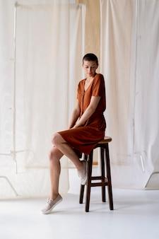 Volledig geschoten vrouw zittend op een stoel