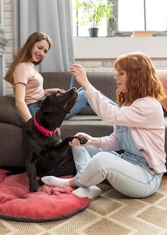 Volledig geschoten vrouwen die met hond spelen