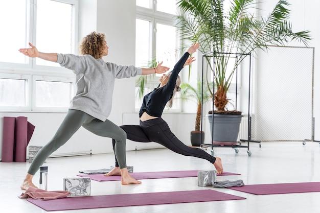 Volledig geschoten vrouwen die samen yoga doen