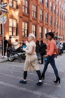 Volledig geschoten vrouwen die straat oversteken