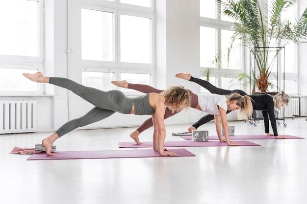Volledig geschoten vrouwen die yoga binnen doen