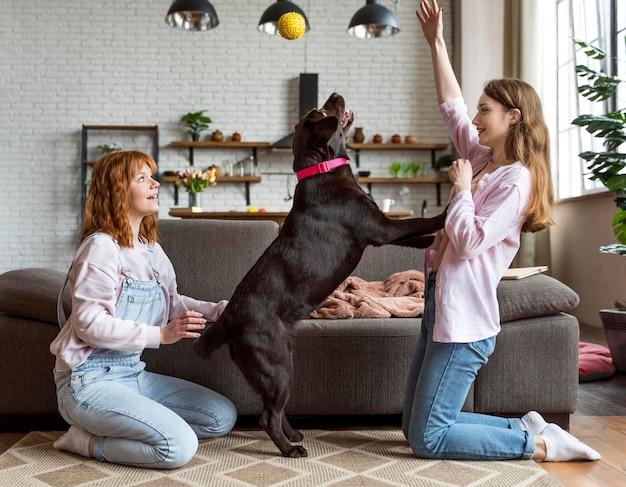Volledig geschoten vrouwen en hond die samen spelen