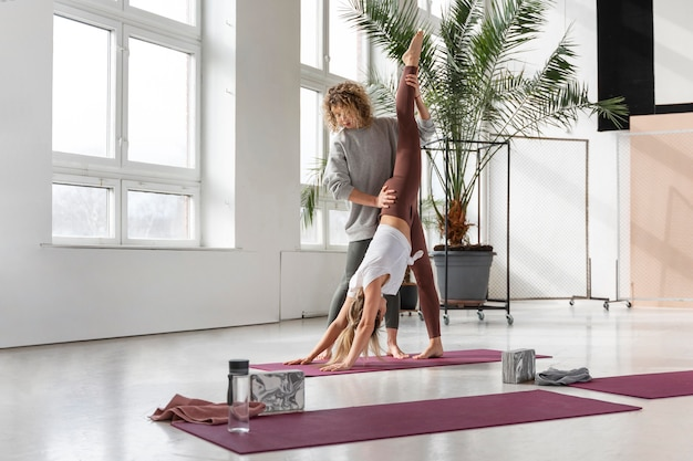 Volledig geschoten yogaleraar die vrouw helpt
