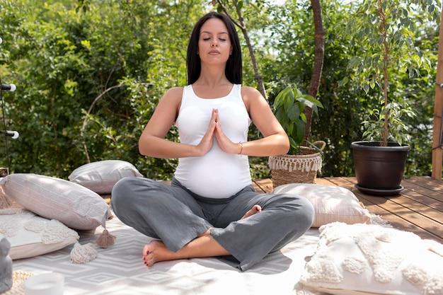 Volledig geschoten zwangere vrouw die mediteert