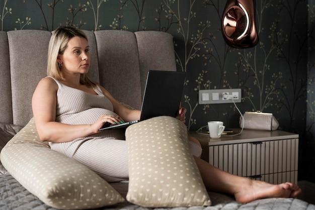 Volledig geschoten zwangere vrouw met laptop