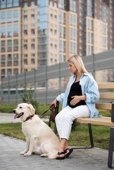 Volledig geschoten zwangere vrouw met schattige hond