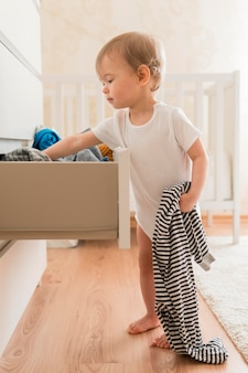Volledig geschotene baby die kleren van lade neemt