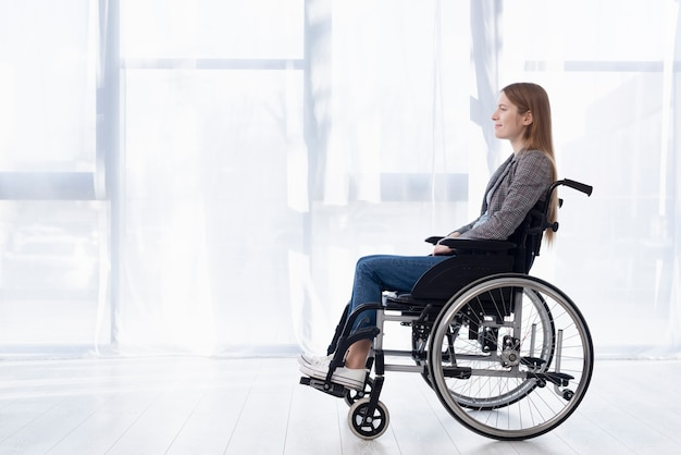 Volledig geschotene jonge vrouw in rolstoel