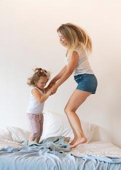 Volledig geschotene moeder en dochter die in bed springen