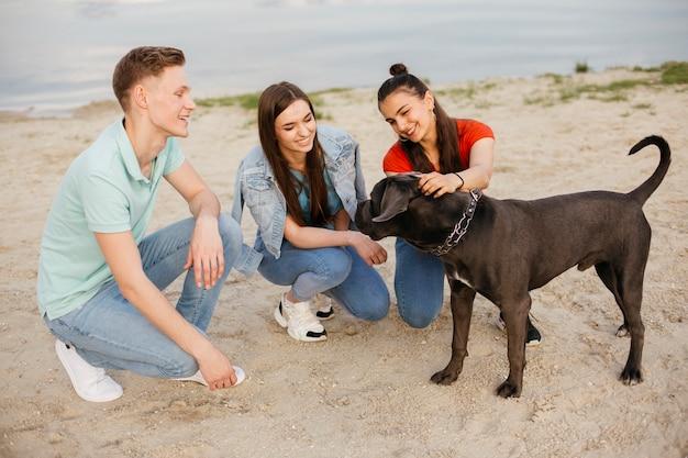 Volledig geschotene vrienden die met mooie hond spelen
