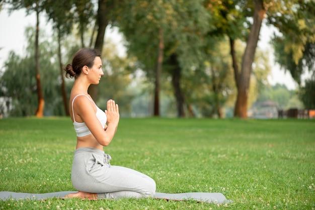 Volledig geschotene vrouw beoefenen van yoga op mat