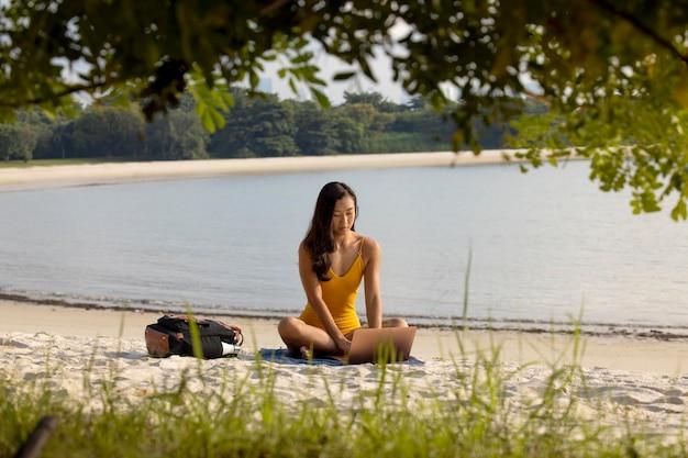 Volledig geschotene vrouw die bij strand zit