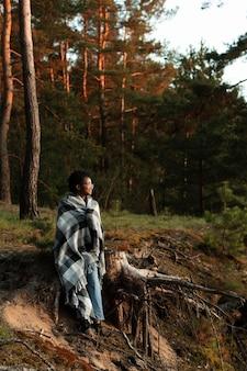 Volledig geschotene vrouw die in bos zit