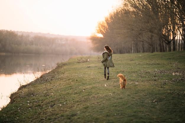 Volledig geschotene vrouw die met hond loopt