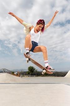 Volledig geschotene vrouw die met skateboard springt