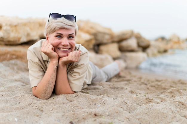 Volledig geschotene vrouw die op het strand legt