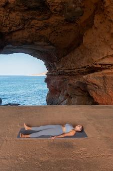 Volledig geschotene vrouw die op yoga mt . legt