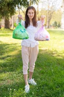 Volledig geschotene vrouw die plastic zakken met afval houdt