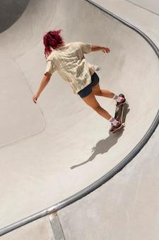 Volledig geschotene vrouw die trucs doet bij skatepark