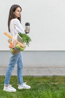 Volledig geschotene vrouw die weg kijkt en herbruikbare zak en thermosfles buiten houdt