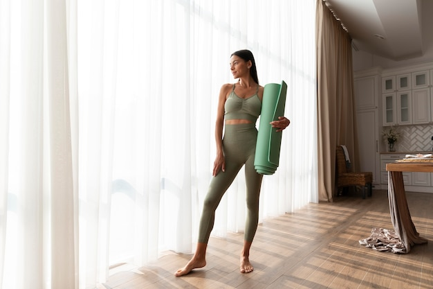 Volledig geschotene vrouw die yogamat houdt