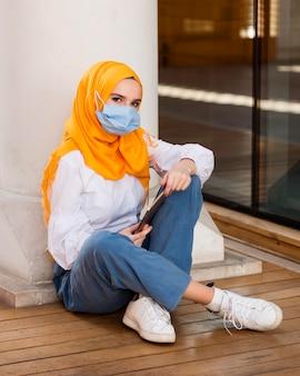 Volledig geschotene vrouw op vloer die masker draagt
