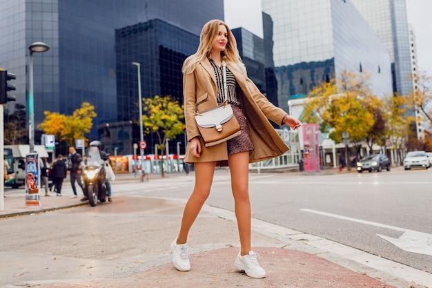 Volledig hoogteportret van het vrij blonde vrouw stellen over stedelijk. beige jas en witte sneakers dragen. trendy accessoires. zorgeloze dame die langs de straat loopt.