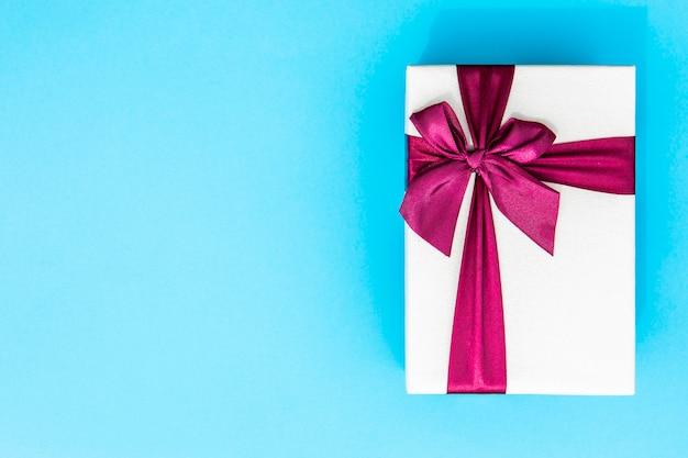 Volledig ingepakt cadeau met lint blauwe achtergrond
