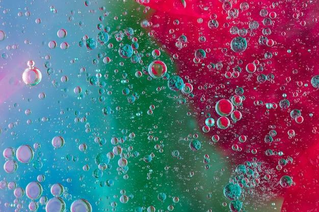 Volledig kaderschot van oliebellen die op multi gekleurde achtergrond drijven