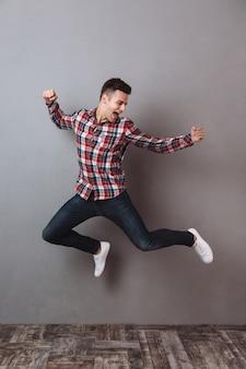 Volledig lengtebeeld van de gelukkige mens in overhemd en jeans het springen