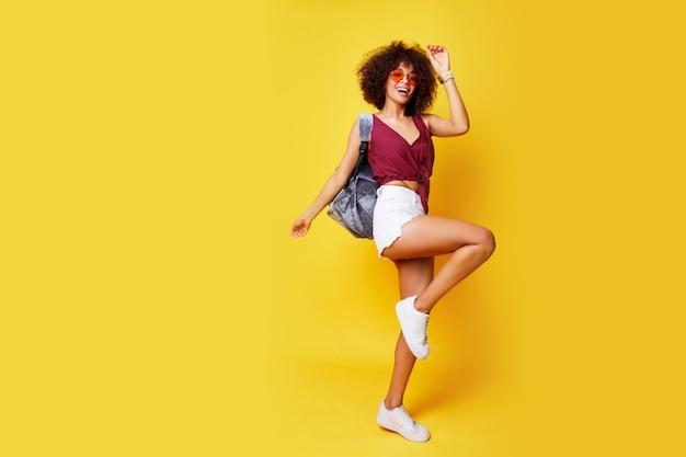 Volledig lengtebeeld van gelukkige actieve gemengde rasvrouw die op geel springt