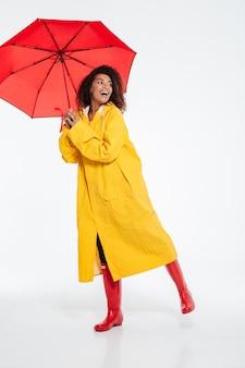 Volledig lengtebeeld van gelukkige afrikaanse vrouw in het regenjas stellen