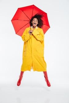 Volledig lengtebeeld van gelukkige gillende afrikaanse vrouw in regenjas