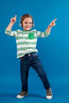 Volledig lengtebeeld van gelukkige jonge jongen het luisteren muziek