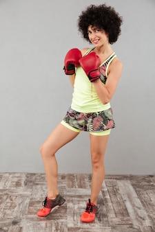 Volledig lengtebeeld van glimlachende sportenvrouw in bokshandschoenen