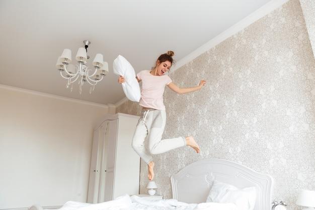 Volledig lengtebeeld van jonge vrouw die pret op bed hebben