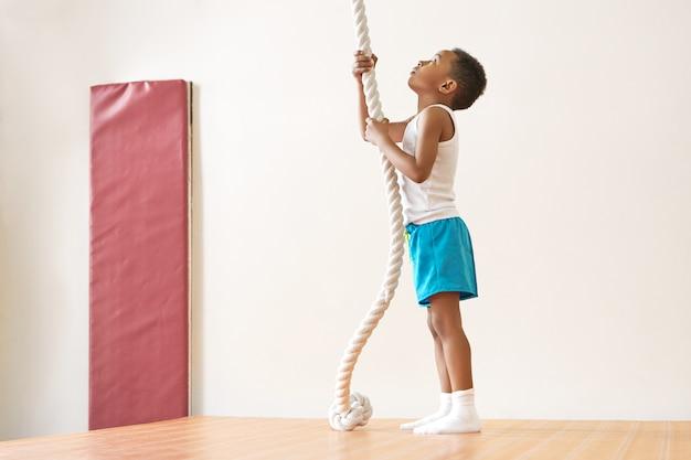 Volledig lengtebeeld van knappe magere afrikaanse amerikaanse schooljongen die witte sokken draagt