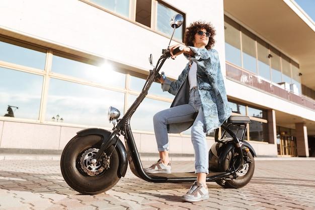 Volledig lengtebeeld van mooie glimlachende krullende vrouw in op moderne motor zitten in openlucht en zonnebril die weg kijken