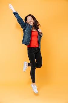 Volledig lengtebeeld van vrolijke aziatische vrouw in denimjasje