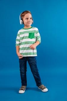 Volledig lengtebeeld van vrolijke jonge jongen het luisteren muziek