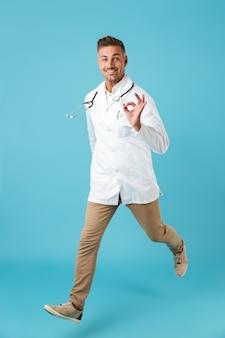 Volledig lengtebeeld van vrolijke mens die witte medische laag en stethoscoop dragen die, terwijl geïsoleerd over blauwe muur lopen