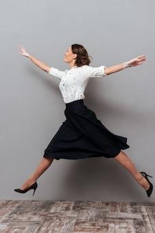 Volledig lengtebeeld van vrouw in bedrijfskleren die en in studio op grijs springen lopen