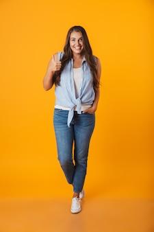 Volledig lengteportret dat van een glimlachende jonge te zware vrouw, duimen toont