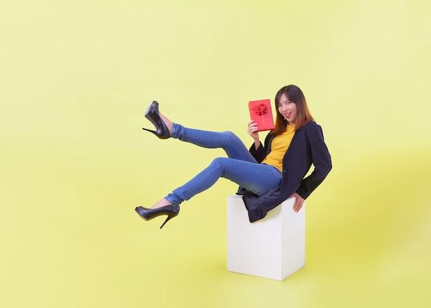 Volledig lengteportret de aantrekkelijke jonge gift die van de vrouwenholding geïsoleerde gele achtergrond zweven