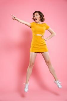 Volledig lengteportret die van geschokte charmante donkerbruine vrouw met hand op haar taille die met vinger richten, opzij kijken terwijl het springen over roze