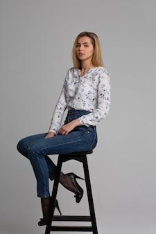 Volledig lengteportret van aantrekkelijke jonge vrouw die klassieke spijkerbroek en wit overhemd draagt