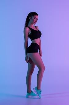 Volledig lengteportret van aantrekkelijke vrouw die zwart trainingspak draagt dat over purpere muur wordt geïsoleerd
