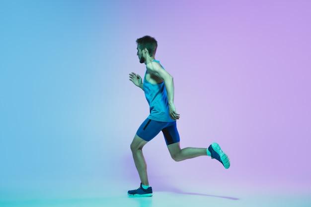 Volledig lengteportret van actieve jonge kaukasische lopende, joggende mens op gradiëntstudio in neonlicht