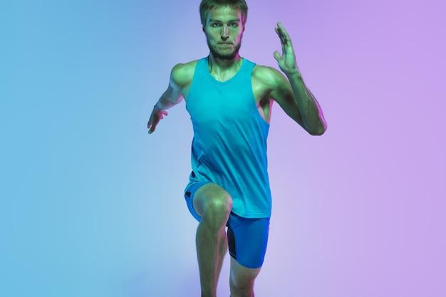 Volledig lengteportret van actieve jonge kaukasische lopende joggingmens op achtergrond in neon
